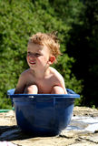 Bath time. Smiling toddler boy taking a bath in a blue plastic tub royalty free stock images