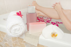 Bath time - cosmetics, towel and soap composition with woman bat. Hing in rose petals in the background Stock Image