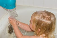 Bath time - little girl in the tub. Child`s bath time - cute little blonde girl in the tub with running water stock image