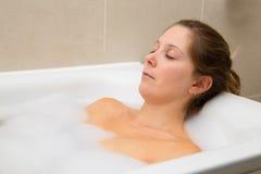 Bath time. Young woman enjoying a bath stock image