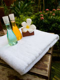Bath towel, bath jel and candle flower shape as spa set. On wooden table Royalty Free Stock Image