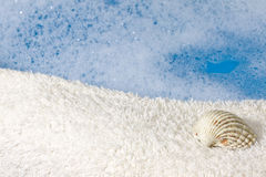 Bath  towel  and shell background Stock Image