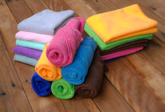 Bath towels. Colorful rolled bath towels on wooden background Stock Image