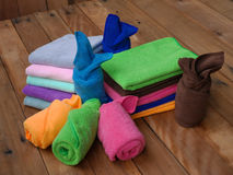 Bath towels. Colorful rolled bath towels on wooden background Royalty Free Stock Photography