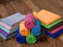 Bath towels. Colorful rolled bath towels on wooden background Royalty Free Stock Image