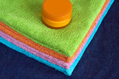 Bath towels of different colors and cream on cotton background Stock Photos