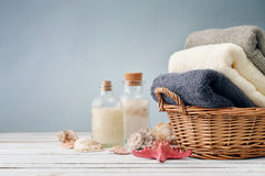 Bath towels. Of different colors in wicker basket with sea shells on light background royalty free stock photo