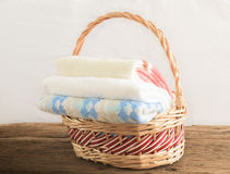 Bath towels of different colors in wicker basket Stock Images