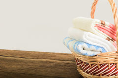 Bath towels of different colors in wicker basket Royalty Free Stock Photo