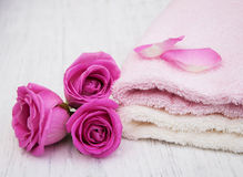 Bath towels with pink roses. On a old wooden background Stock Image