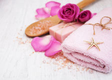 Bath towels, salt and soap. With pink roses on a old wooden background Royalty Free Stock Photos