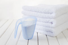 Bath towels and washing powder in measuring cup Stock Photos