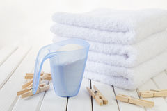 Bath towels, washing powder in measuring cup and wooden clothesp Stock Image
