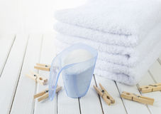 Bath towels, washing powder in measuring cup and wooden clothesp Royalty Free Stock Images