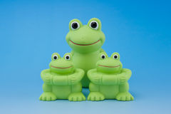 Bath toys. On blue background - three frog toys Royalty Free Stock Images