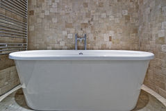 Bath tub. Free standing contemporary ceramic bath tub and stone tile wall Stock Photography