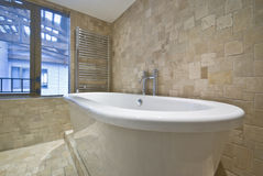 Bath tub detail with stone tiled walls. Detail of a contemporary bath tub with natural stone tiled walls and floor stock image