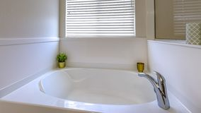 Bath tub in middle class home that is clean. And spacious. The tub is blank white with a plant and golden cup sitting in the corner. Blank white tile stock images