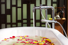Bath tub with water and flowers stock photography