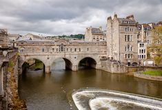 Palladian Pulteney Bridge and the weir at Bath Somerset South We. BATH, UK - JUN 11, 2013: View of Palladian Pulteney Bridge and the weir on the River Avon Royalty Free Stock Image