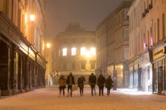 The High Street at night in snow, with people walking stock photos