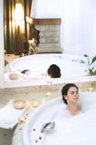 Bath in a whirlpool hot tub jacuzzi. Young woman enjoys the bath-foam in a whirlpool hot tub jacuzzi royalty free stock image