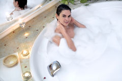 Bath in a whirlpool hot tub jacuzzi. Young woman enjoys the bath in a whirlpool hot tub jacuzzi royalty free stock photos