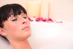 Bath woman. Caucasian woman lyig in tub and finding balance while relaxing in a lot of foam Stock Photos