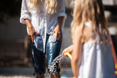 Bath in the yard with moother. Girl pours water on her Mom royalty free stock images