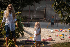 Bath in the yard with moother. Girl pours water her  Mom stock photography