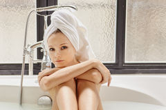 In the bath. Young woman relaxing at the bathroom in bath Royalty Free Stock Photography