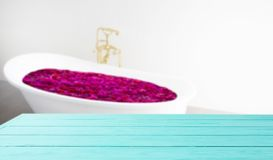 Bathed in flower bath ritual. Blue wooden shelf on bathroom background. Wood desk table with top view and copy space white bath. At hotel. Room service and royalty free stock image