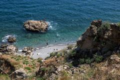 Bathers jump of a rock island off the beach at Konyaalti Plaji in Antalya in Turkey. Royalty Free Stock Photography