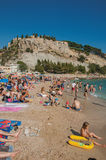 Bathers on the pebble beach with castle in the background in Cassis. Stock Photography