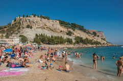 Bathers on the pebble beach with castle in the background in Cassis. Royalty Free Stock Photos