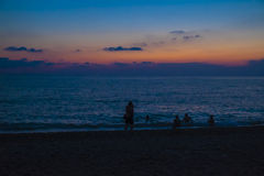 Bathers on a sea beach after sunset Royalty Free Stock Photography