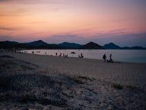 Bathers at sunset on a sandy beach of south Sardinia. Stock Photos