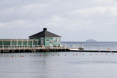 Bathhouse. A bath house at the sea . In the background is a cruise ship Stock Image