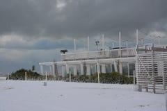 Bathhouse i vinter med snö på stranden i en medelhavs- semesterort royaltyfria bilder