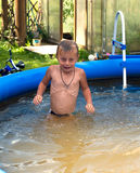 Bathing. The boy bathes in dark blue inflatable pool Stock Images