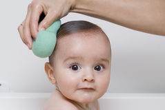 Bathing the baby with the sponge. Royalty Free Stock Image