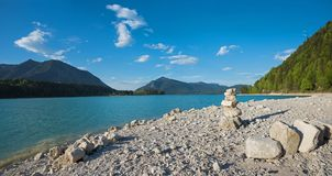 Bathing beach lake walchensee with stack of boulders. cold mount Royalty Free Stock Photos