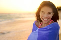 Bathing beach woman with towel happy portrait. Young pretty mixed race Asian Caucasian girl wrapped in towel standing in beach sunset. Smiling happy enjoying stock image