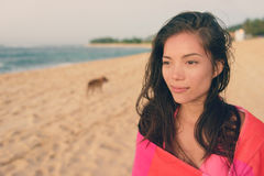 Bathing beach woman with towel relaxing portrait. Young pretty biracial Asian Caucasian girl wrapped in towel standing in beach sunset. Female enjoying summer royalty free stock images