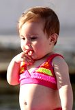Bathing Beauty Baby. Dark haired 9 Month old baby girl in pink bikini bathing suit at the water. Shallow depth of field Stock Photos