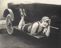 Bathing beauty posing on running board of convertible Stock Images