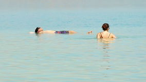 Bathing in the Dead Sea. Dead Sea, Israel - May 22, 2017: People are bathing and swimming in the Dead Sea. The salinity of the dead sea water makes people stock footage