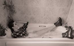 Bathing fully clothed. Young woman chilling in the bath Royalty Free Stock Image