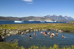 Bathing in hot spring in beautiful Landscape with Icebergs and Mountains, Greenland. Tourists and locals bathing in hot springs with icebergs in background in stock photos