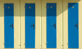 Bathing hut. Four blue doors of yellow bathing huts on a beach, with strong shadow Royalty Free Stock Photo